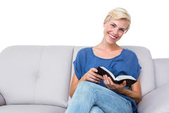 Attractive blonde woman reading a book on the couch Stock Images