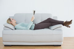 Attractive blonde woman reading newspaper lying on couch Royalty Free Stock Images