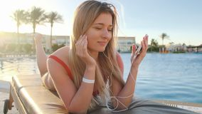 Attractive blonde woman in red swimsuit dancing, listening music from her smartphone, while lying on deck chair in hotel. Attractive blonde woman in red swimsuit stock video footage