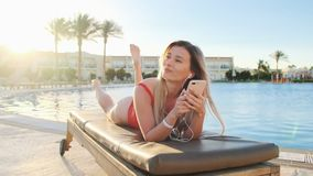 Attractive blonde woman in red swimsuit shaking head, listening music from her smartphone, while lying on deck chair in. Hotel swimming pool side area. Girl stock video footage