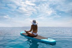 Blonde woman relaxes in a yoga position on a stand up paddle board SUP. Attractive, blonde woman relaxes in a yoga position on a stand up paddle board SUP over stock photos