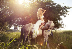 Beautiful photo of blonde sensual bride riding a horse. Attractive blonde woman riding a horse in sunny day wearing white dress in garden Stock Image