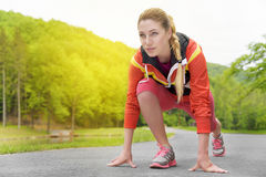 Attractive blonde woman running on track outdoors Stock Photos