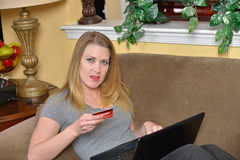 Attractive blonde woman shops on-line with laptop Stock Photos