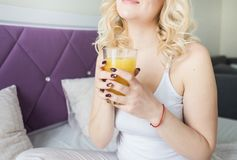 Attractive blonde woman sits on the edge of the bed at home and holds a stocker with orange juice in her hand. Morning royalty free stock photography