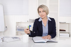 Attractive blonde woman sitting at desk. Stock Photos
