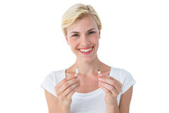 Attractive blonde woman snapping cigarette and smiling at camera Stock Images