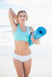 Attractive blonde woman in sportswear carrying an exercise mat Royalty Free Stock Image