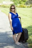 Attractive blonde woman with suitcase - disability. Attractive blonde woman in blue dress who is missing part of left arm (congenital amputation) standing on stock photo
