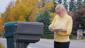 Attractive blonde woman takes the mail from the mailbox. Countryside in USA