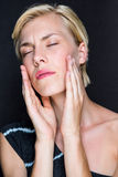 Attractive blonde woman touching her face Stock Image