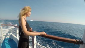 Attractive blonde woman tourist on boat watching the sea enjoying breeze on a summer day of vacation  -. Attractive blonde woman tourist on boat watching the sea stock video