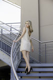 Attractive blonde woman on urban staircase Royalty Free Stock Image