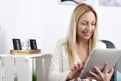 Attractive blonde woman using tablet in office. Work in the office stock images