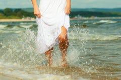 Blonde woman wearing dress walking in water Stock Photo