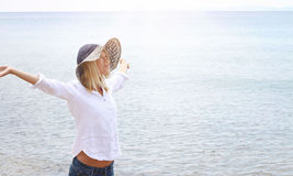 Attractive blonde woman wearing white shirt and straw hat breathing Happy With Raised Arms. Freedom concept. Hazy light image Royalty Free Stock Photo