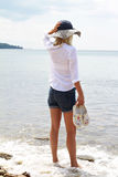 Attractive Blonde Woman wearing white shirt and straw standing and enjoying view on the beach near sea Stock Image