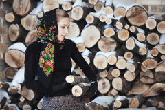Attractive blonde woman on winter veranda on firewood background Royalty Free Stock Image