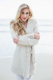 Attractive blonde woman in wool cardigan looking at camera Royalty Free Stock Photography