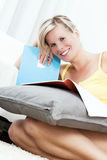 Attractive blonde woman writing in the home. Royalty Free Stock Image