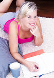 Attractive blonde woman writing in the home. Royalty Free Stock Photography