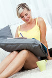 Attractive blonde woman writing in the home. Stock Photos