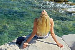 Attractive Blonde Women  on the stone coast, beach, sea, ocean, enjoying summer holidays and vacation, beautiful woman sunbathing, Stock Images