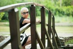 Attractive blonde on the wooden bridge crouching Stock Photos