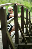 Attractive blonde on the wooden bridge crouching Stock Photography
