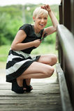 Attractive blonde on the wooden bridge crouching Royalty Free Stock Photos