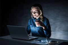 Attractive Blonde Working On Laptop In Dark Office. Mixed Media Stock Photo