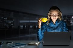 Attractive Blonde Working On Laptop In Dark Office. Mixed Media Royalty Free Stock Photo