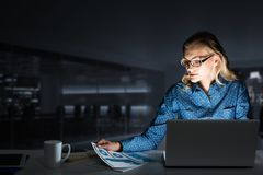 Attractive Blonde Working On Laptop In Dark Office. Mixed Media Stock Images