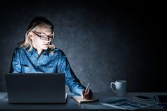 Attractive Blonde Working On Laptop In Dark Office. Mixed Media Stock Photography