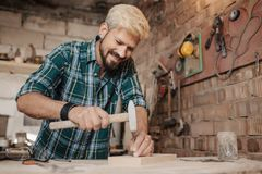 Attractive blonde young hipster bearded man by profession carpenter builder nailing wood board with hammer on a wooden. Young hipster bearded man by profession Royalty Free Stock Images