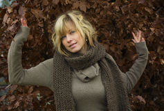 Attractive blonde young woman against autumn leaves. Wearing wool clothes royalty free stock image