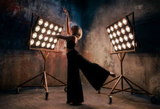 Attractive blonde young woman dancer on the stage with lights in loft background. Portrait of beautiful attractive blonde young woman dancer on the stage with stock photography