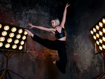 Attractive blonde young woman dancer on the stage with lights in loft background. Portrait of beautiful attractive blonde young woman dancer on the stage with stock images