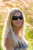 Attractive blonde young woman in a park. With blurred background Stock Images