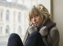 Attractive blonde young woman sitting next to window. Elegant building in background Stock Photos