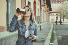 Attractive blonde young woman walking on the street, using her smartphone and drinking coffee Royalty Free Stock Images