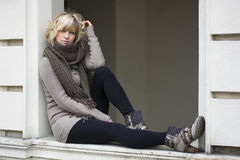 Attractive blonde young woman on window sill Stock Images