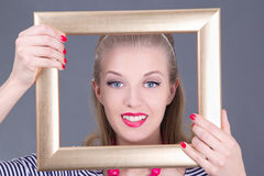 Attractive blondie pinup girl in striped dress with photo frame Royalty Free Stock Image