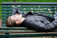 Attractive blue eyed, blond young man laying on park bench Royalty Free Stock Photography