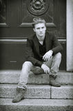 Attractive blue eyed, blond young man sitting on stair steps Royalty Free Stock Images