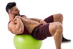 Muscleman exercising abs on an exercise ball Stock Photos