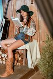 Attractive bohemian girl reading a book sitting on a bench in a royalty free stock photo
