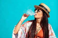 Attractive bohemian girl smoking cigarette and exhaling smoke. Isolated on turquoise royalty free stock images