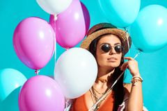 Attractive bohemian girl standing with helium balloons royalty free stock photos