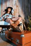 Attractive bohemian woman sitting on a bench with legs on suitcase in wooden. House stock images